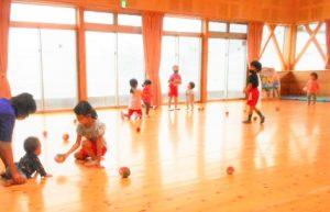 遊戯室でソフトボールを使って遊ぶ園児